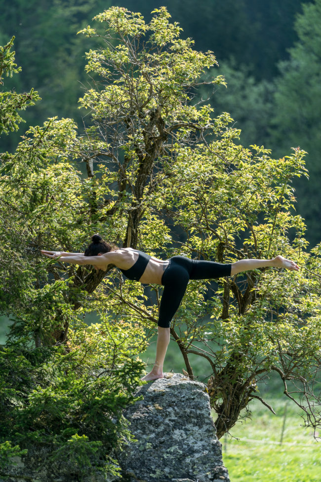 un'atleta pratica yoga in un bosco